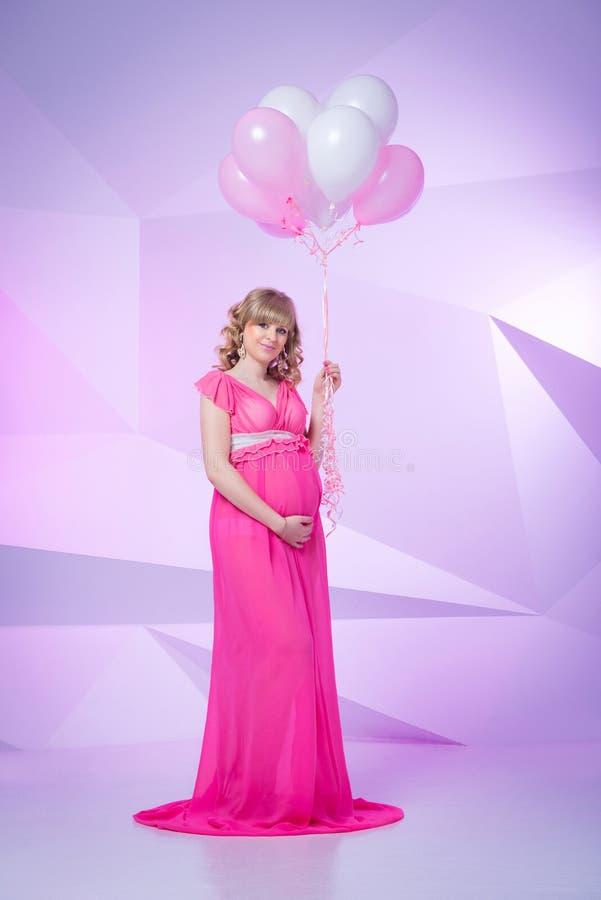 Härligt och lyckligt gravid kvinnaanseende i studio med ballonger på rosa bakgrund royaltyfri bild