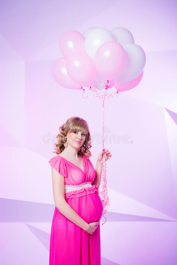 Härligt och lyckligt gravid kvinnaanseende i studio med ballonger på rosa bakgrund arkivbilder