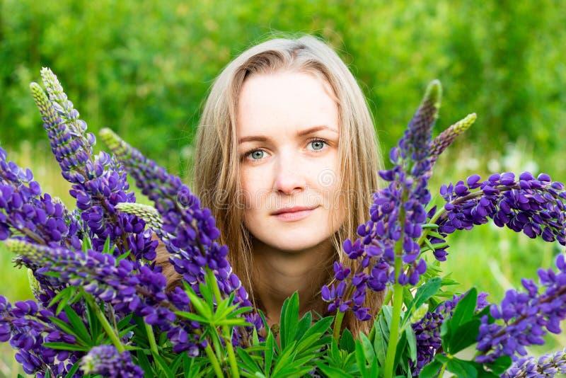 Härligt och ung flicka bland de härliga blommorna av lupin royaltyfria foton