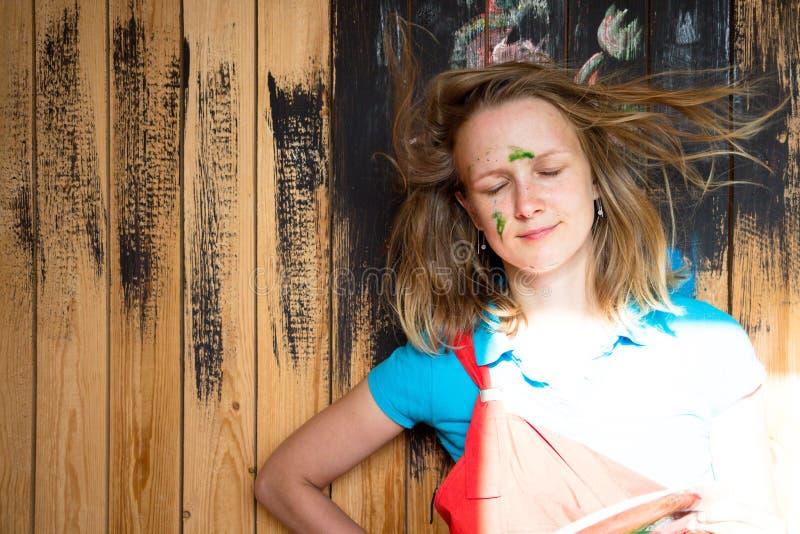 Härligt och unga flickan står på en träväggbakgrund som målas med svart målarfärg Framsidan för flicka` s befläckas med gre arkivfoton