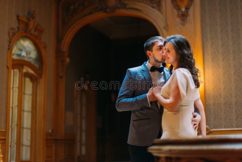 Härligt omfamna för brölloppar och kyssande near balustrad på ursnygg antik trappa med bakgrunden av kungliga personen arkivfoto