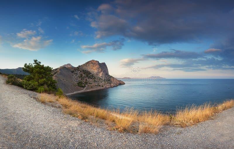 Härligt panorama- landskap med berg, bana, gult gräs fotografering för bildbyråer