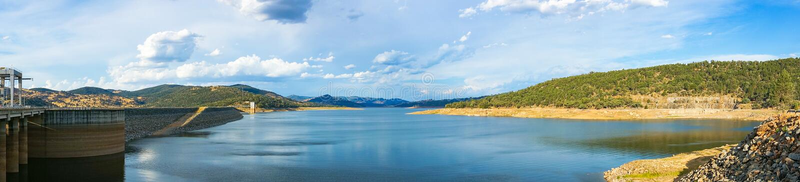 Härligt panoramalandskap av sjön och fördämningen som omges av kullar arkivbilder