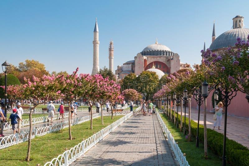Härligt parkera gränden med turister och den Hagia Sophia gränsmärket på bakgrunden arkivfoto