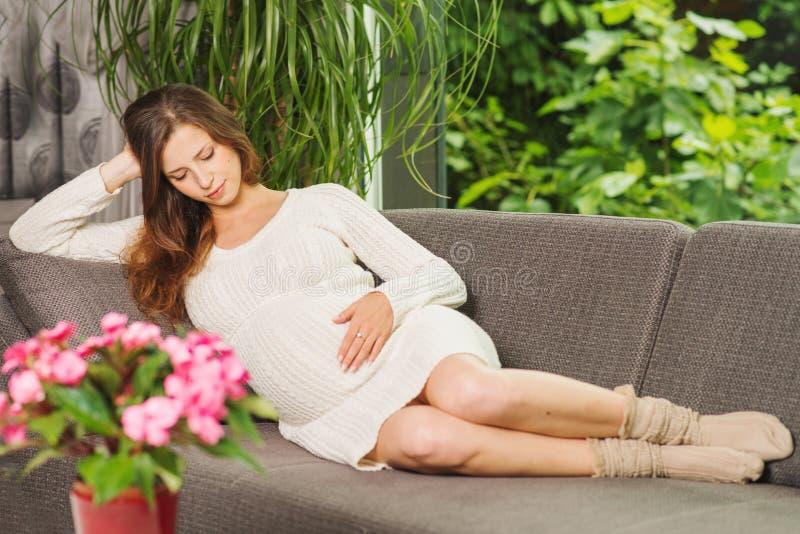 Härligt pregnangtkvinnasammanträde på soffan royaltyfria bilder