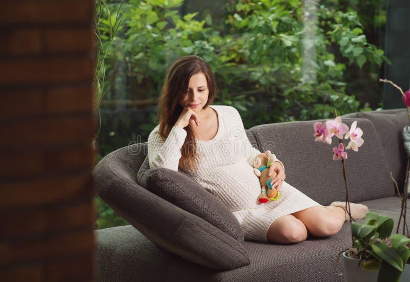 Härligt pregnangtkvinnasammanträde på soffan royaltyfri fotografi