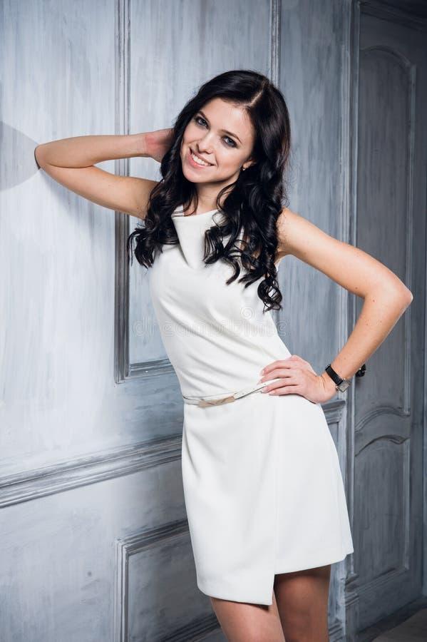 Härligt rikt caucasian anseende för affärskvinna i lyxig vit klänning Neutral vindinre med dunkel belysning Kvinna royaltyfria foton