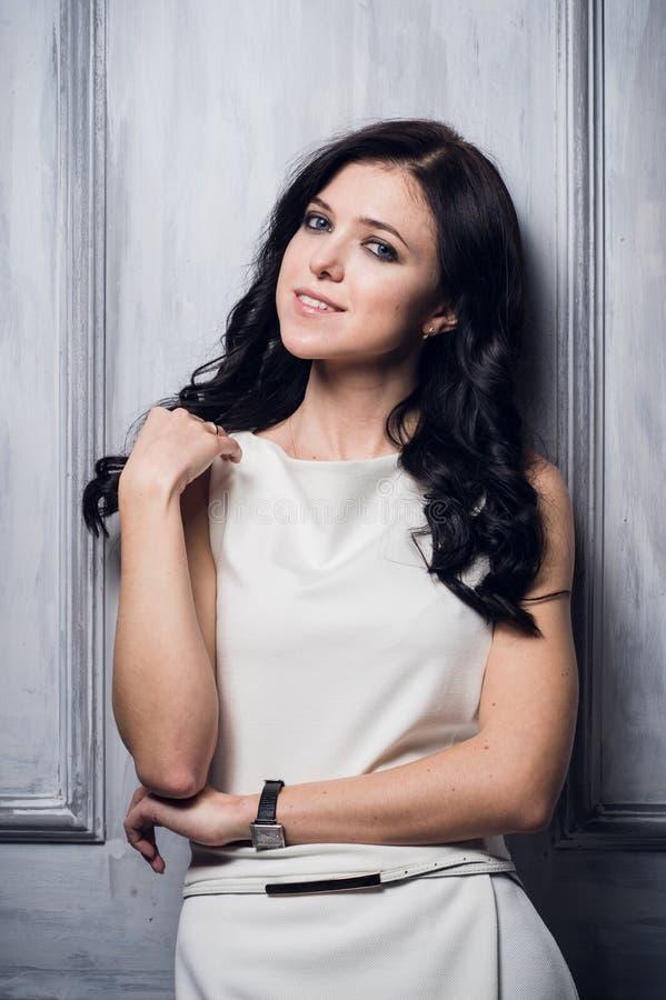 Härligt rikt caucasian anseende för affärskvinna i lyxig vit klänning Neutral vindinre med dunkel belysning Kvinna royaltyfria bilder