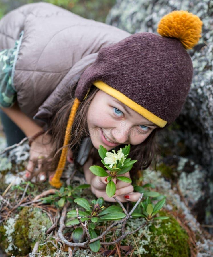 Härligt romantiskt brunettflickaanseende i blommande trädgård Drömma prinsessan i felik klänning som luktar blommorna royaltyfria foton