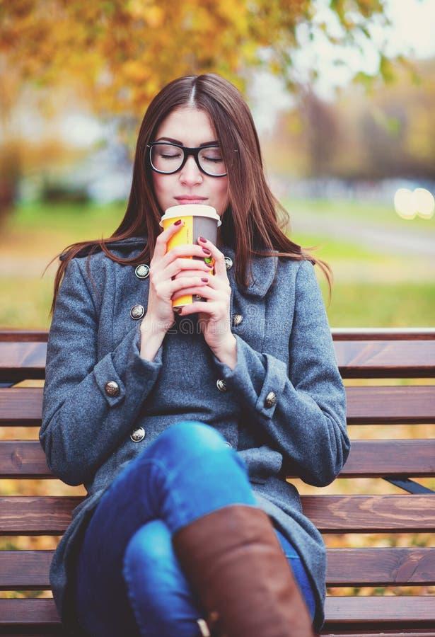 Härligt sammanträde för den unga kvinnan på en bänk som dricker kaffe eller det varma höstlaget för te som in tycker om, parkerar royaltyfria bilder