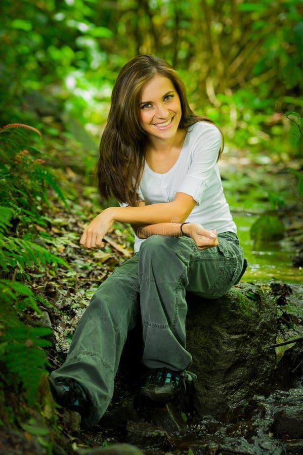 Härligt sammanträde för ung kvinna i djungeln royaltyfria bilder