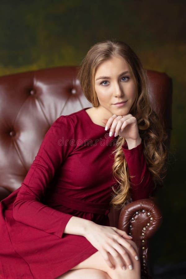 Härligt sammanträde för ung kvinna i fåtölj inomhus Se i c royaltyfri fotografi