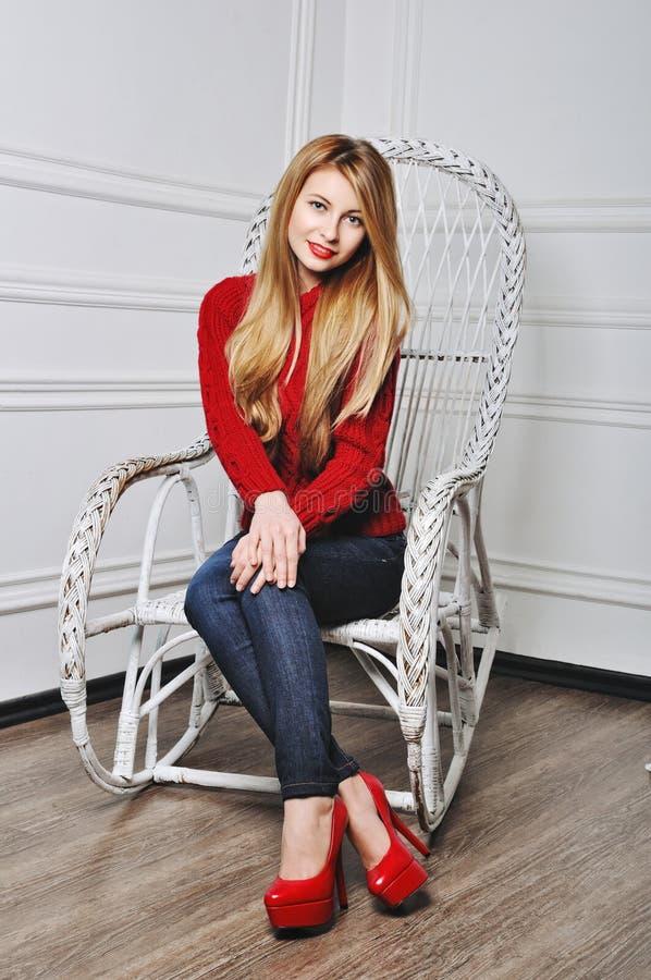 Härligt sammanträde för ung kvinna i moderiktiga skor Ben i röd hög häl royaltyfri bild