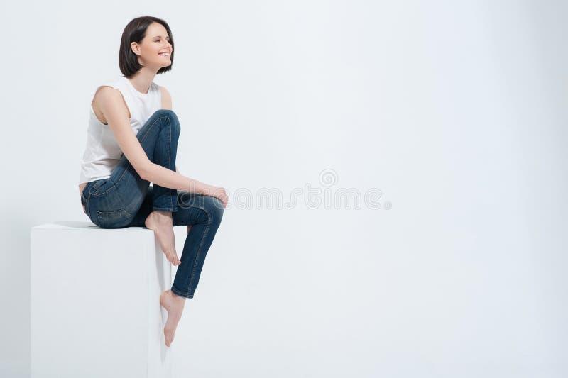 Härligt sammanträde för ung kvinna på den vita kuben i studio royaltyfri foto