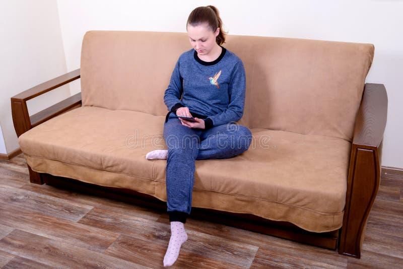 Härligt sammanträde för ung kvinna på en soffa, genom att använda en smartphone och smsa Koppla av på soffan hemma royaltyfri foto