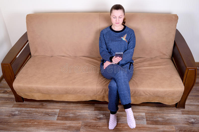 Härligt sammanträde för ung kvinna på en soffa, genom att använda en smartphone och smsa Koppla av på soffan hemma arkivbilder