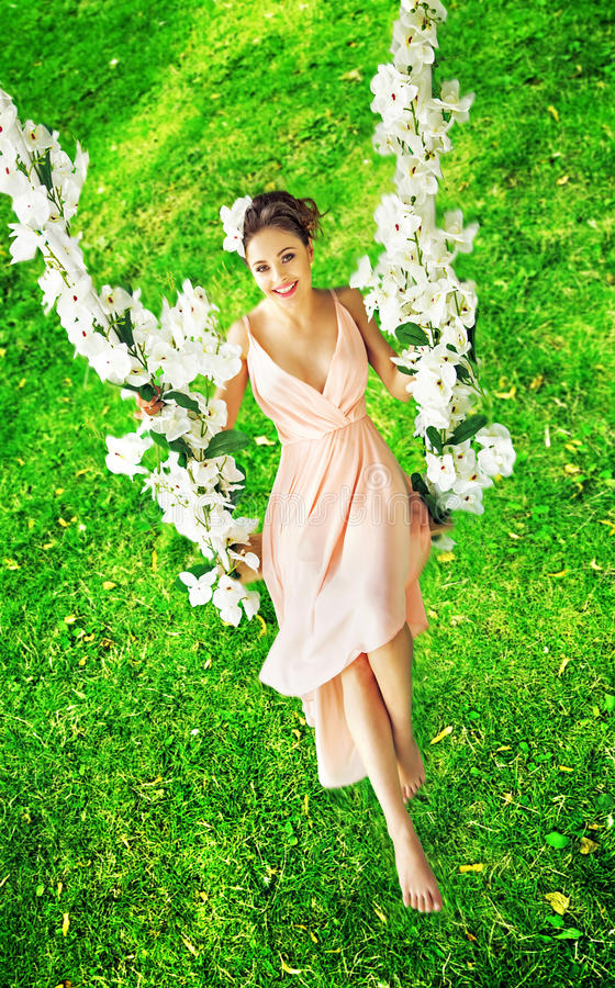 Härligt sammanträde för ung kvinna på gungbrädet royaltyfria foton
