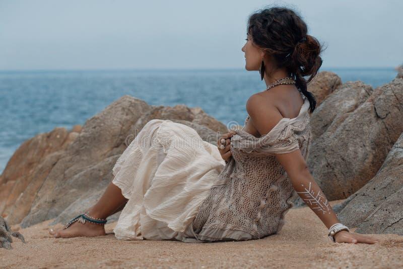 Härligt sammanträde för ung kvinna på sand på stranden arkivbild