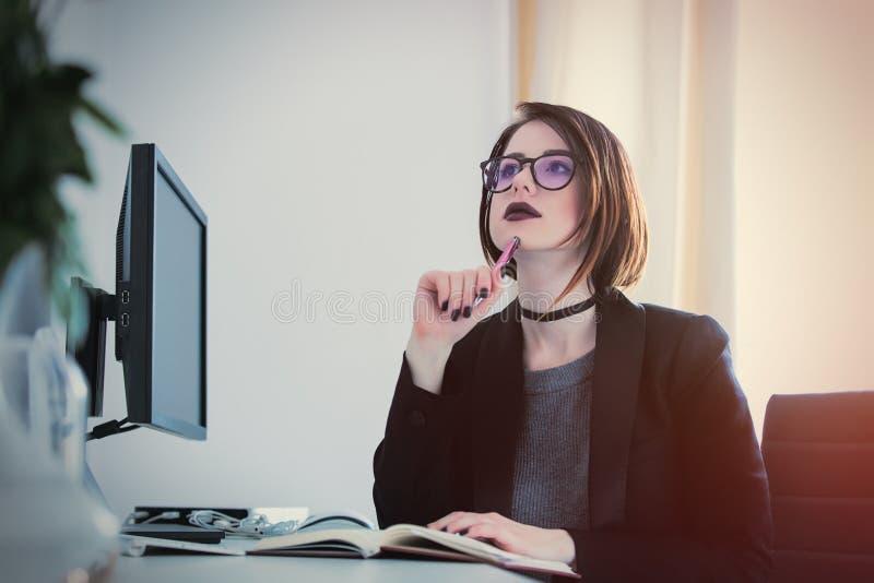 Härligt sammanträde för ung kvinna på skrivbordet och tänka i Co arkivfoto