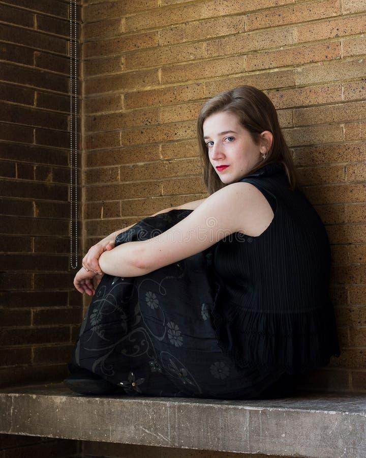 Härligt sammanträde för ung kvinna på stenbänk mot tegelstenväggen fotografering för bildbyråer