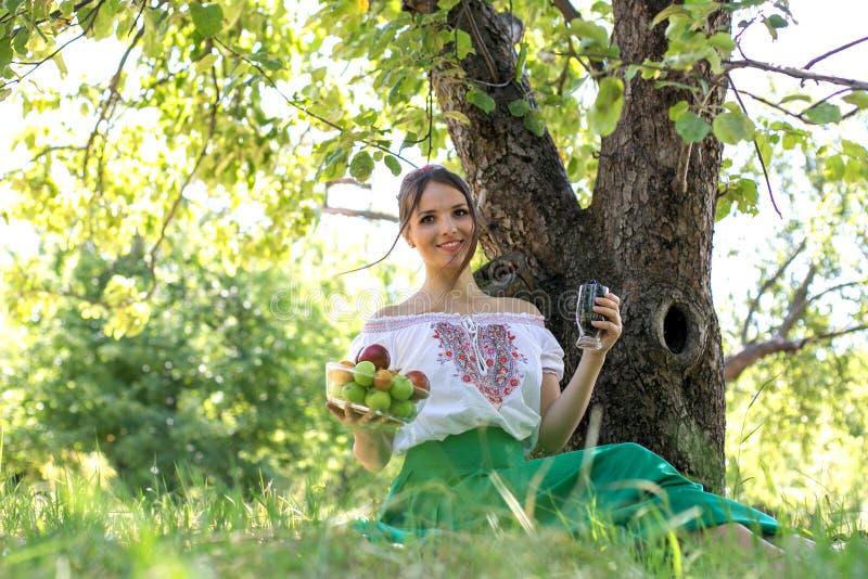 Härligt sammanträde för ung kvinna under ett träd med en platta av frukt och ett exponeringsglas av energii royaltyfri fotografi