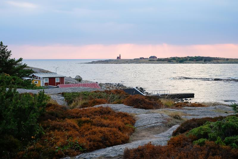 Härligt scandinavian landskap med stenar och mossa Traditionella röda svenska hus Hav på solnedgången, fyren på royaltyfri bild