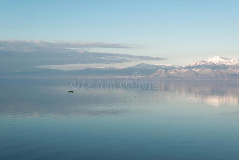 Härligt sceniskt landskap av Shkodra sjön, bergreflexionen och lite fiskebåten arkivbild