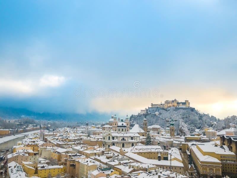 Härligt sceniskt vinterlandskap i historisk stad av Salzburg med snöig tak, domkyrkor och den berömda fästningen Hohensalzburg b arkivfoto