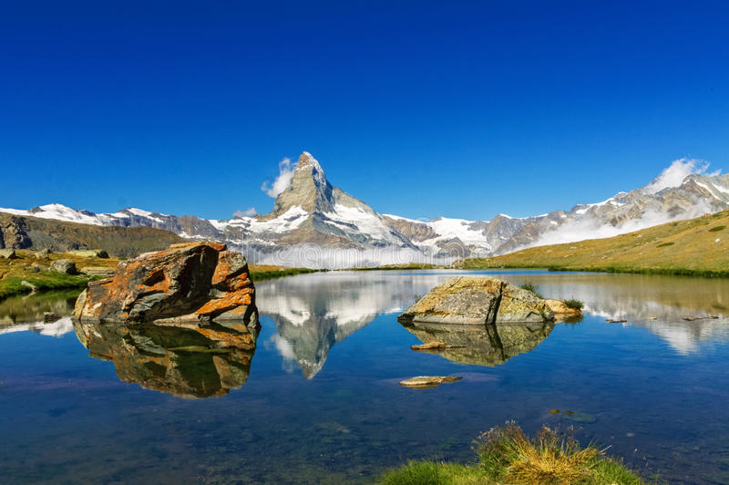 Härligt schweiziskt fjällänglandskap med sjö- och bergreflexion i vatten royaltyfri fotografi