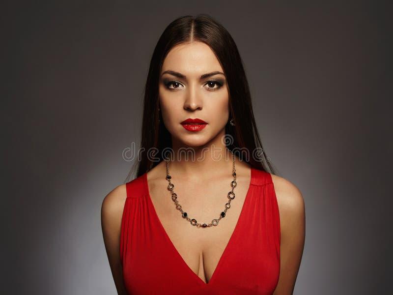 härligt sexigt kvinnabarn Skönhetbrunettflicka med smink Röd klänning royaltyfri fotografi