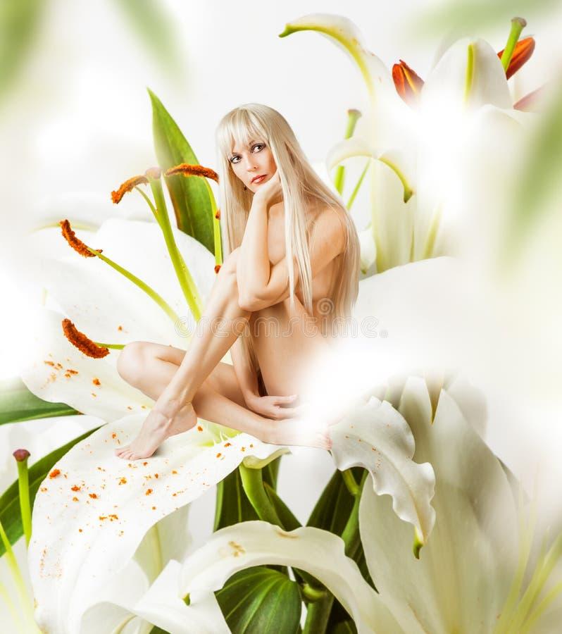 Härlig sexig kvinnaskälmskt naturväxen i blommor royaltyfri foto