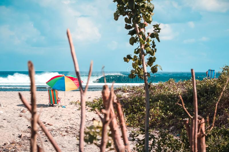 Härligt skott av en strand med en färgrik slags solskydd och en strandstol med att förbluffa vågor royaltyfri fotografi