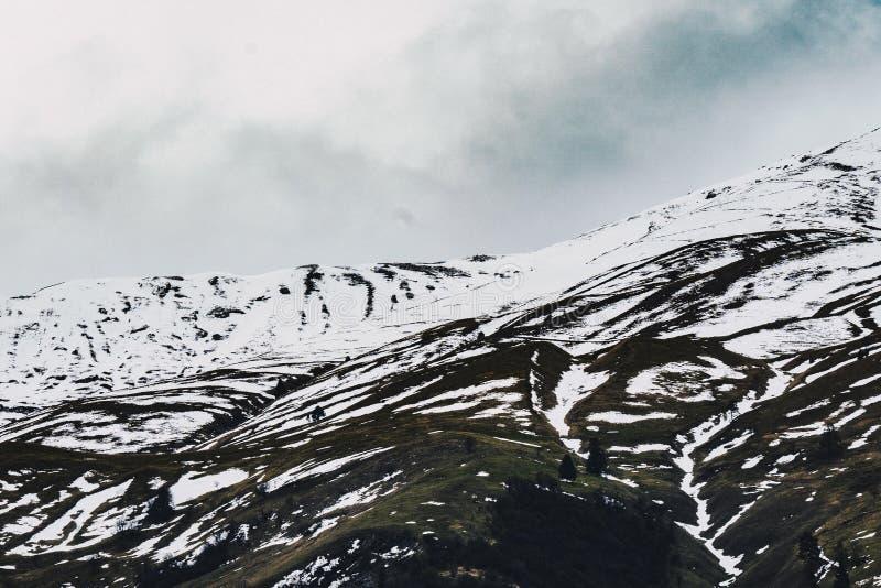Härligt skott av snöig kullar med molniga himlar royaltyfri foto