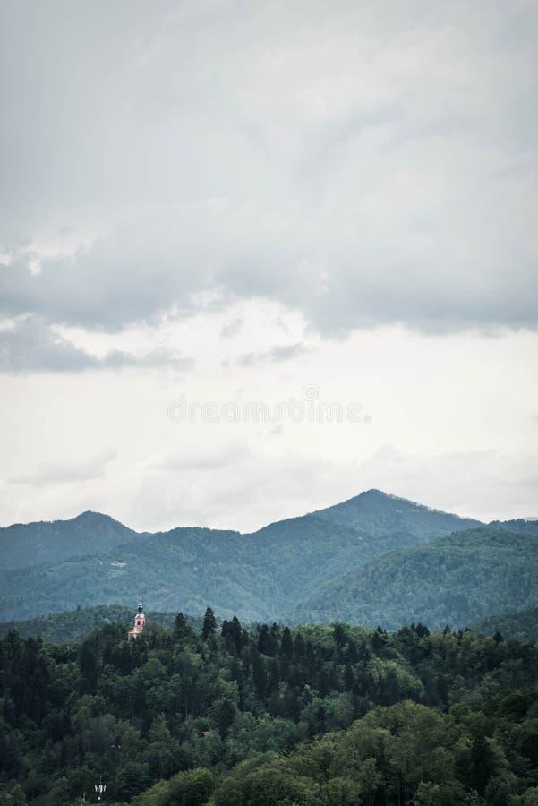 Härligt skott för långt område av gröna berg och skogen och moln på överkanten royaltyfri illustrationer