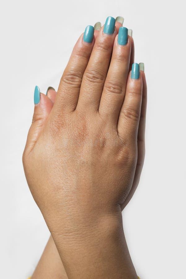 Härligt slut upp av händer av en ung kvinna med blå manikyr fotografering för bildbyråer