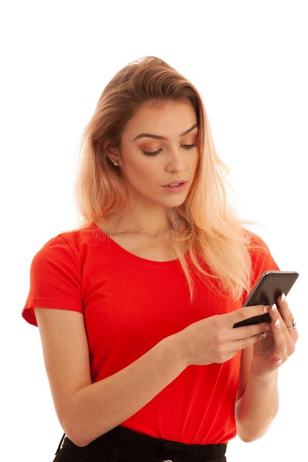 Härligt smsande meddelande för ung kvinna på en smartphone som isoleras över vit bakgrund fotografering för bildbyråer