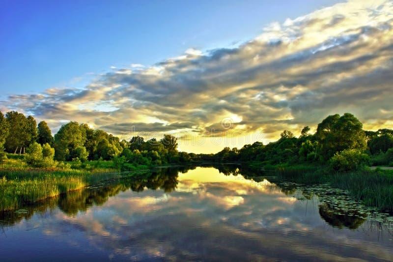 Härligt solnedgånglandskap med reflexion på flodhimmel och moln arkivfoton