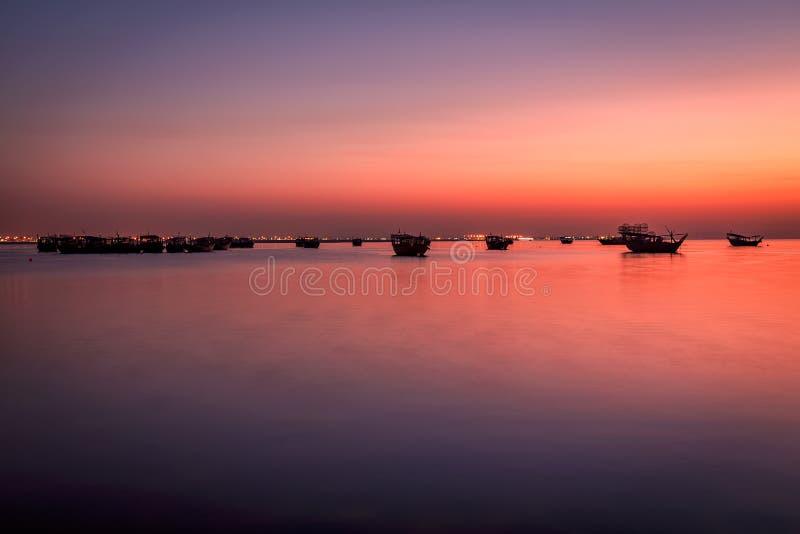 Härligt soluppgångfartyg i sjösida med röd och mörk himmel Dammam - Saudiarabien arkivbild