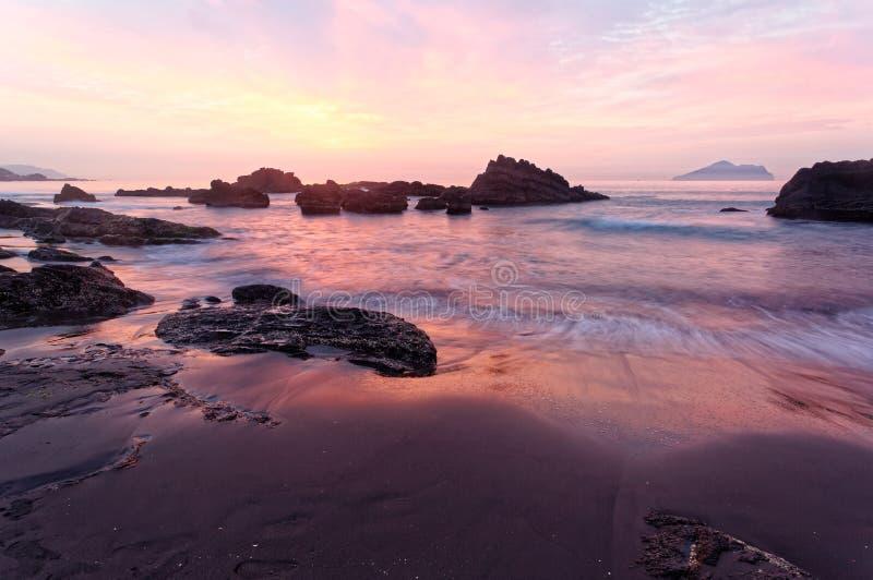 Härligt soluppgånglandskap av en stenig strand i nordliga Taiwan arkivfoton