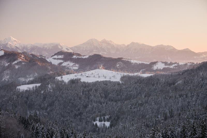 Härligt soluppgånglandskap av helgonet Thomas Church i Slovenien på bergstoppet i den vinter- och Triglav bergbakgrunden royaltyfria foton