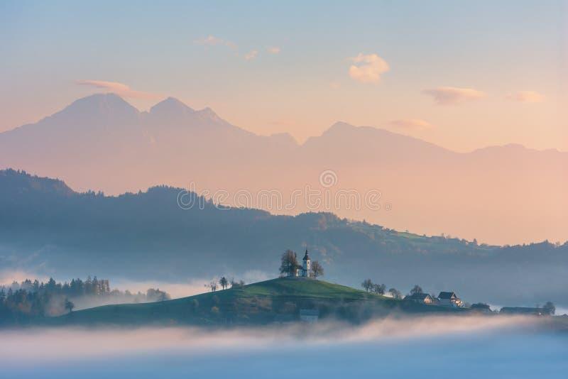 Härligt soluppgånglandskap av helgonet Thomas Church i Slovenien på bergstoppet i morgondimman fotografering för bildbyråer