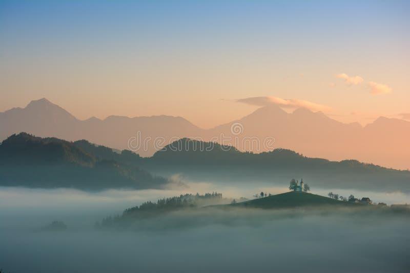 Härligt soluppgånglandskap av helgonet Thomas Church i Slovenien på bergstoppet i morgondimman med orange och blå himmel och Trig royaltyfri foto