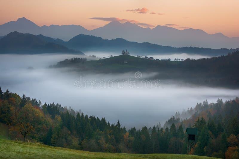 Härligt soluppgånglandskap av helgonet Thomas Church i Slovenien på bergstoppet i morgondimman med rosa och orange himmel och Tri royaltyfri bild