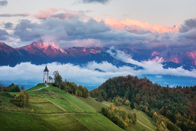 Härligt soluppgånglandskap av kyrkliga Jamnik i Slovenien med molnig himmel royaltyfri fotografi