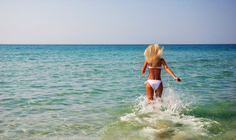 Härligt spensligt ungt kvinnaspring i havet vinkar royaltyfri fotografi