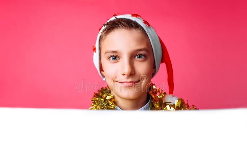 Härligt tonårigt i jultomtenhatt och med glitter på halsen som poserar behi royaltyfri fotografi