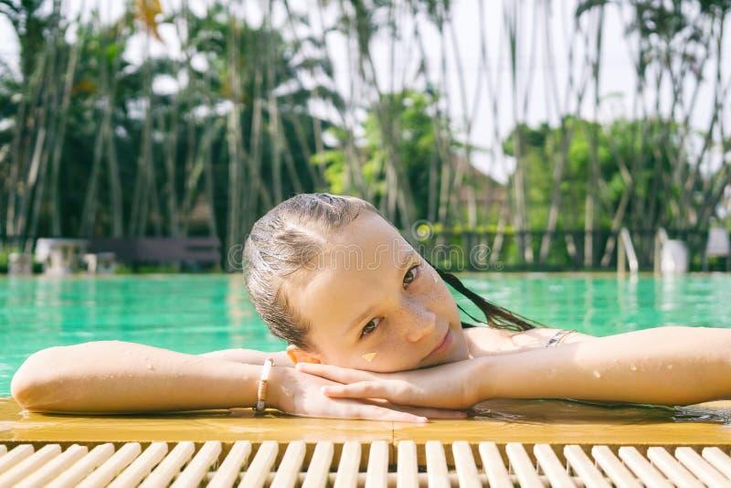 Härligt tonårigt tråkar ut kopplar av på poolsiden i Thailand Se in camera Headshot Skönhet semester, sund livsstil royaltyfri foto