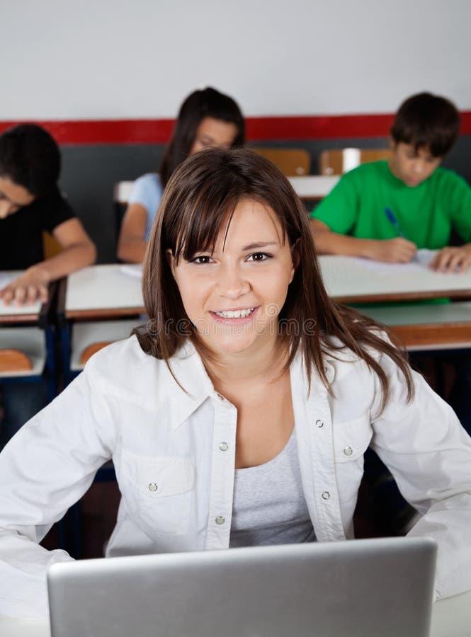 Härligt tonårs- skolflickasammanträde med bärbara datorn arkivfoton