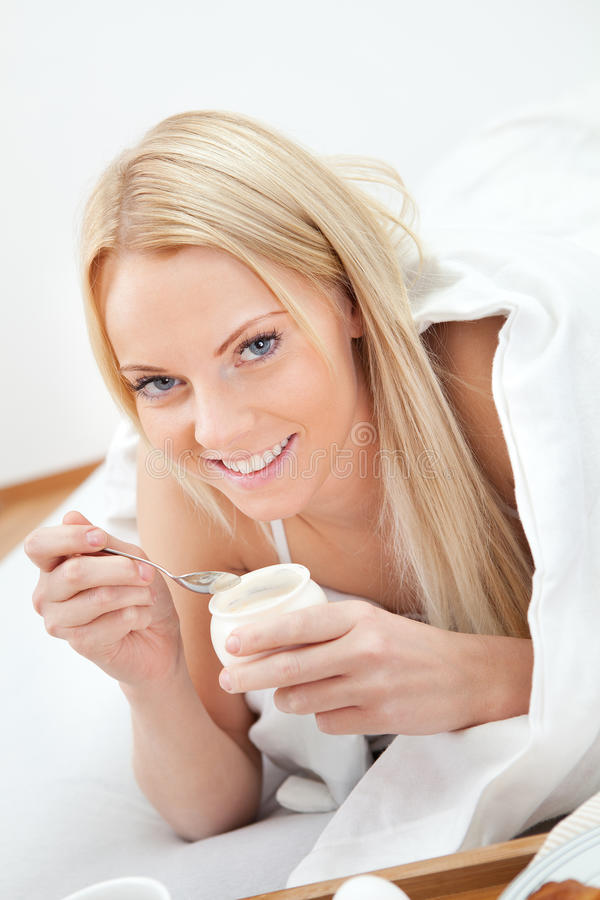 härligt underlag som äter kvinnayoghurt royaltyfri fotografi