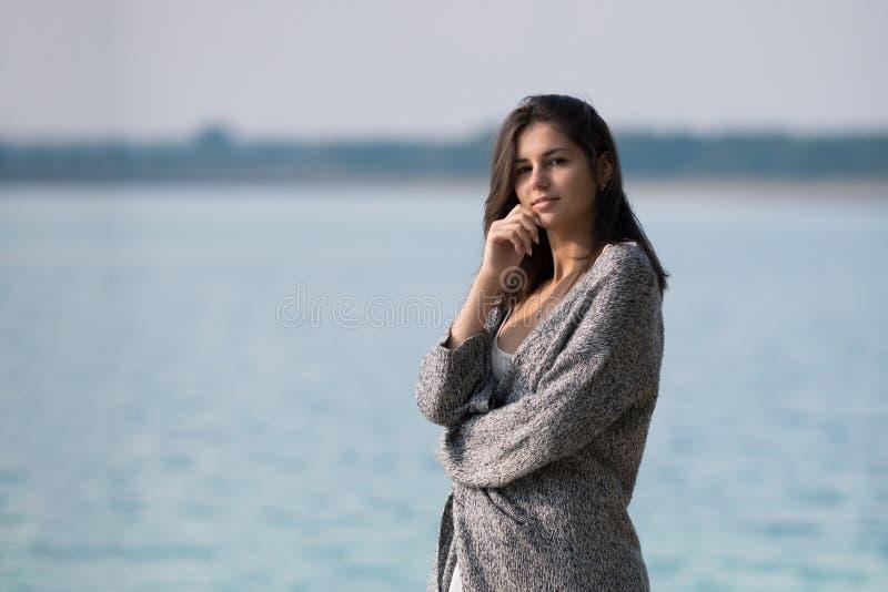 Härligt ung flickaanseende vid sjön arkivfoto